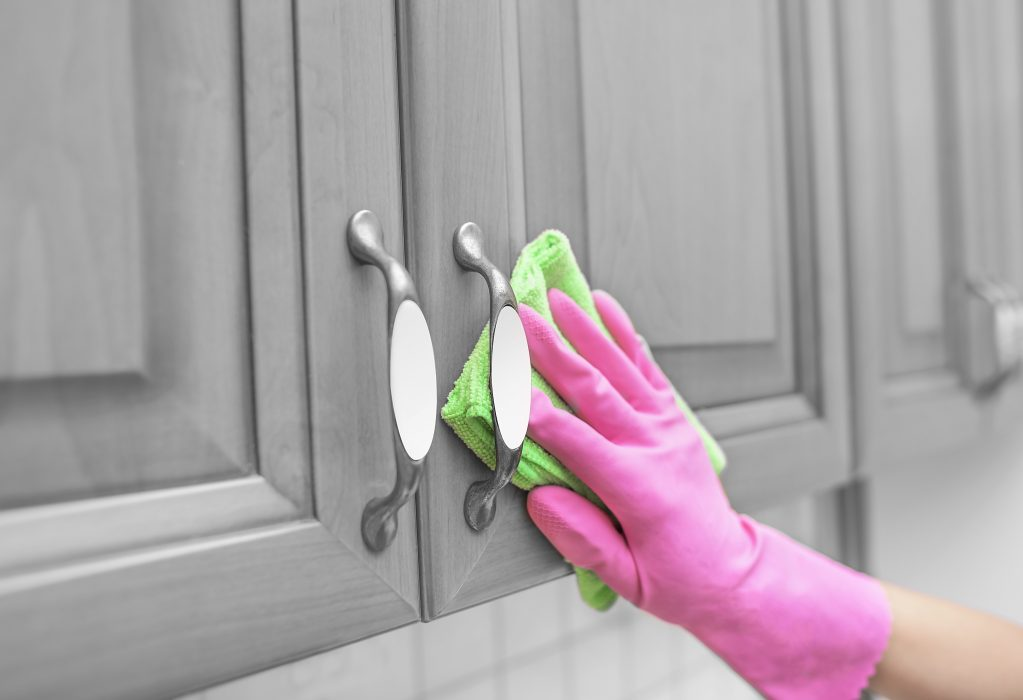 women's gloved hand wipe the dust from the locker door.